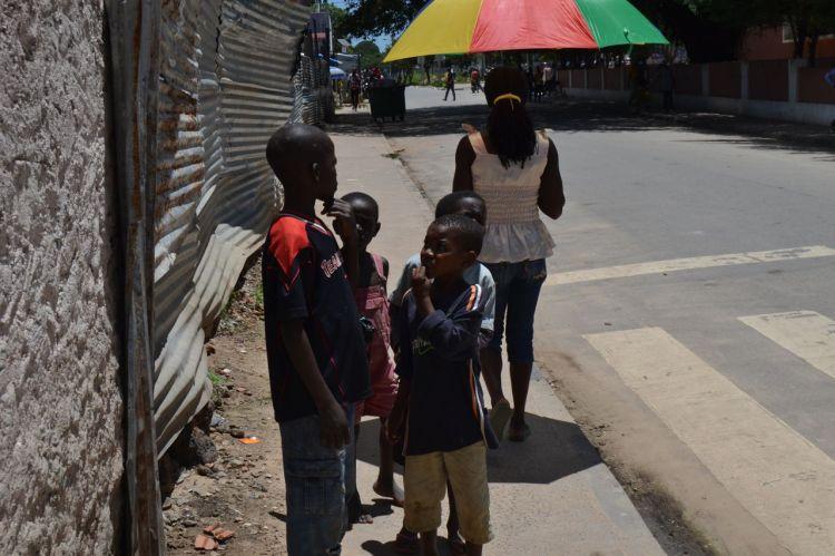 Niños de la calle y chica con paraguas