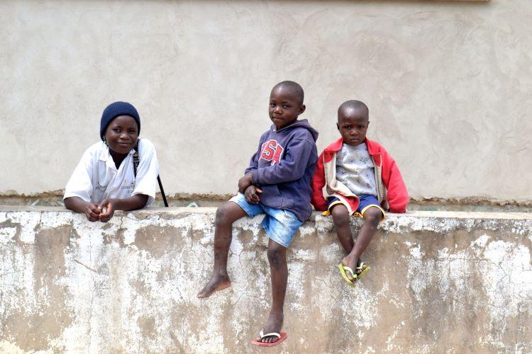 Niños sentados en una tapia en Kuito