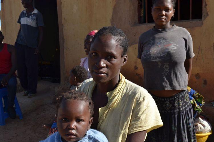 Una mujer y su hijo delante de su casa